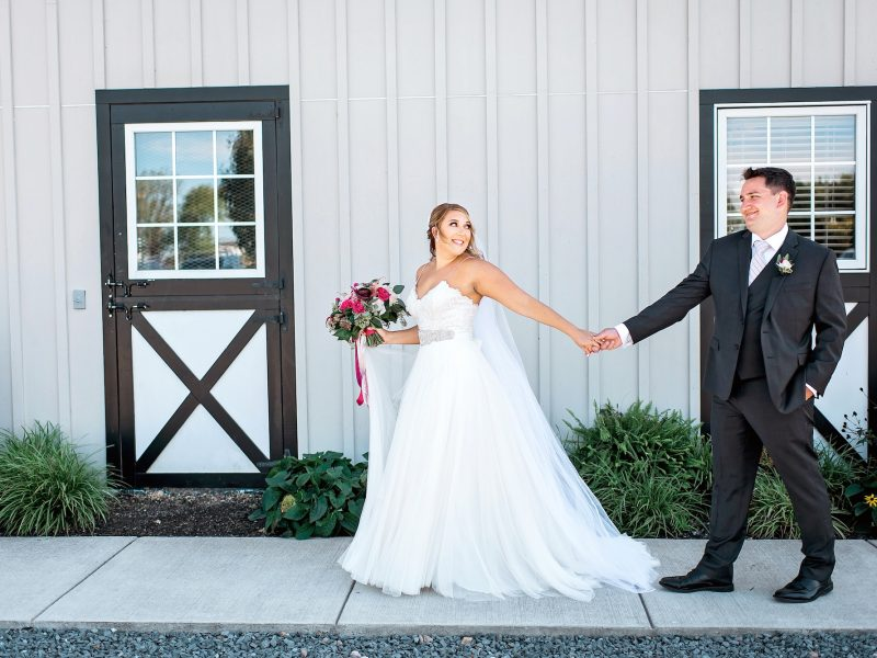 couple holds hands at Shadow Creek barn