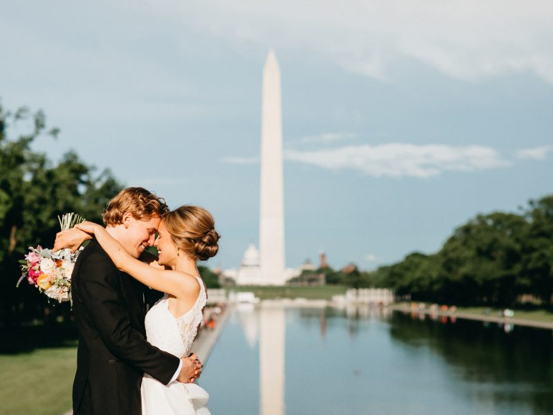 Couple getting married posing by the Washington Monument